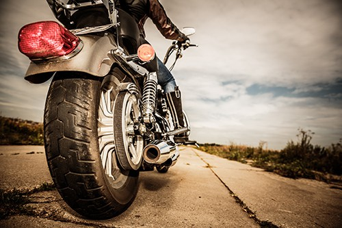 Biker girl riding on a motorcycle. Bottom view of the legs in leather boots. Focus on the rear wheel. | Northglenn Motorcycle Accident Attorney