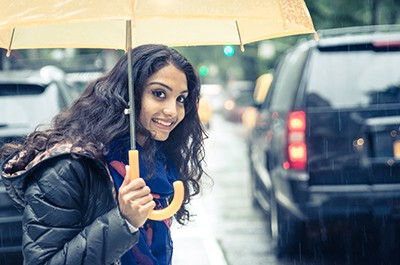 Smiling woman under the rain covering with umbrella in New york | Arvada Premises Liability Attorneys
