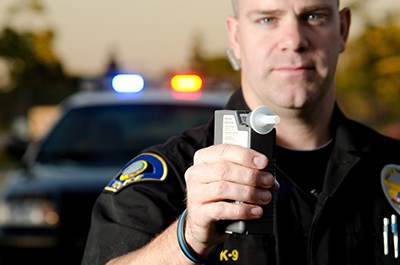 cop holding a breathalyzer | Alcohol Restrictions for all Help Prevent Underage DUI Accidents