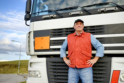 truck-driver-in-front-of-truck | How to Share the Road with Truck Drivers