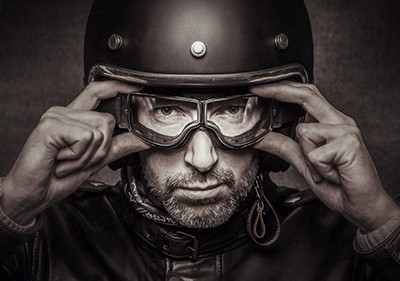 motorcycle rider in vintage gear adjusting googles | Finding the Right Spinal Cord Injury Attorney for Your Motorcycle Accident
