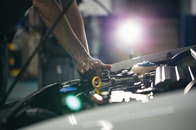 Auto mechanic repair engine in a car repair shop   Finding a Repair Shop After an Accident can be difficult