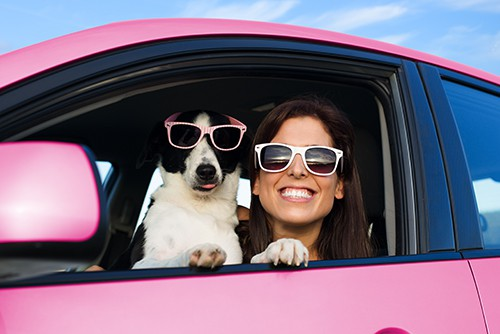 Woman and dog in pink car on summer road trip wearing sunglasses | Interesting Car Color Facts You Might Find Surprising