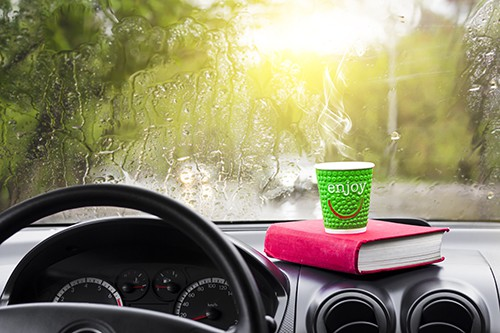 Rainy day in the car window with a glass of hot coffee and a book | Pass the Time on Autonomous Drives