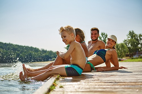 happy family on a dock in summer | how to avoid Summer Accidents