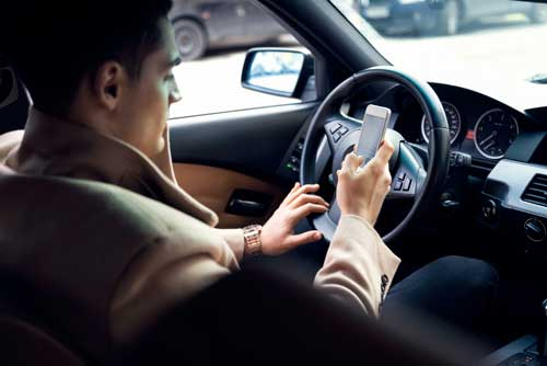 business man in expensive coat texting and driving | New Texting Law in Colorado Raises Concerns