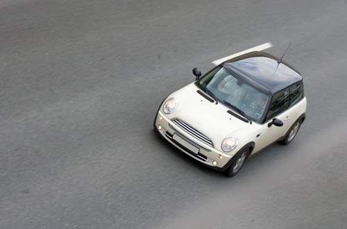 white mini car driving on highway   Are Mini Cars More Dangerous Than Larger Cars?