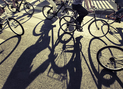 bicyclists and their shadows on the road | Broomfield Bicycle Accident Attorneys