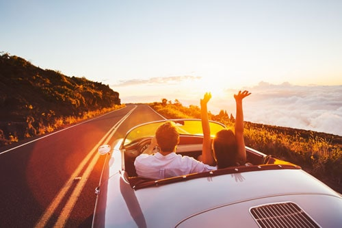 man and woman driving in convertible into the sunset | Labor Day Weekend Travel Safety Tips