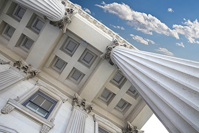 a shot from below looking up at the outside of a courthouse with a partial blue sky | difference between contributory and comparative negligence