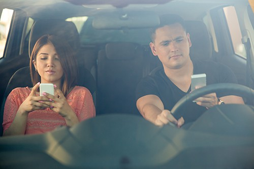 Portrait of a young couple texting and driving together, as seen through the windshield | Distracted Driving in Northglenn
