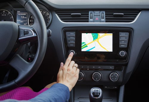 woman using dashboard gps | Which Cars are Most Distracting