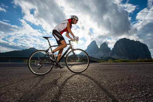 female cyclist biking down highway by rock formations | Broomfield Bicycle Accident Attorneys