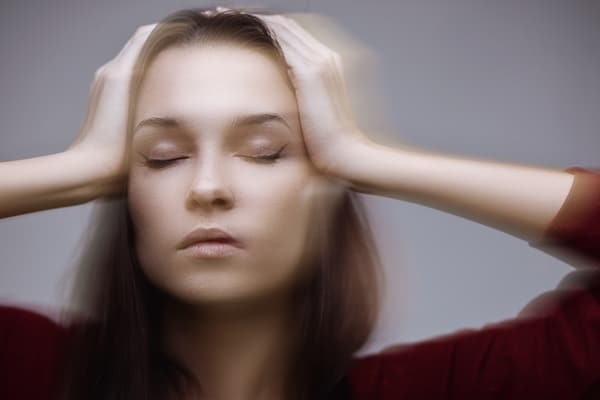 young woman holding her head experiencing Dizziness after a Car Accident