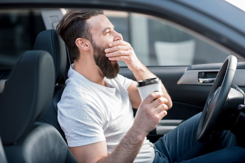 yawning man with a beard holding coffee and Driving While Drowsy