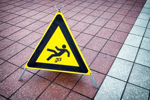 caution wet floor sign on tile floor | How to File a Slip and Fall Claim