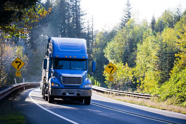 blue semi driving down a country road | Trucking Accidents in Arvada