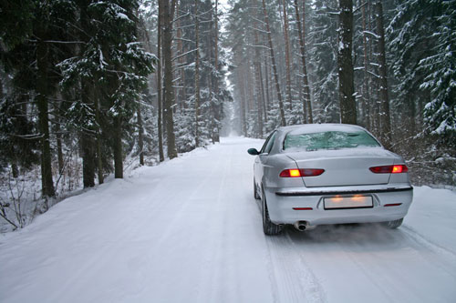 white car driving down snowy forest road | Winter Driving Essentials