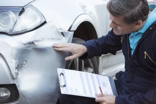 Man checking the damage of a car   Insurance company Tricks and Tactics