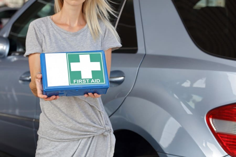 woman holding first aid kit in front of a car | Items You Must Have in Your Car At All Times