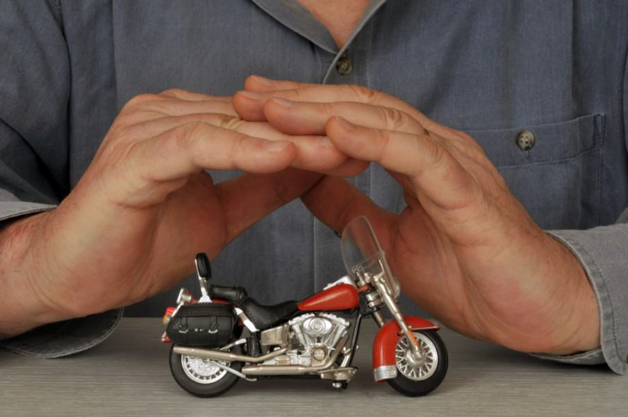 man covering a miniature bike with his hands | Cost to Insure a Motorcycle in Colorado