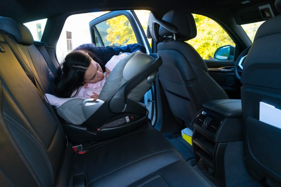 lady putting her baby at the back seat | safest seat in a car accident