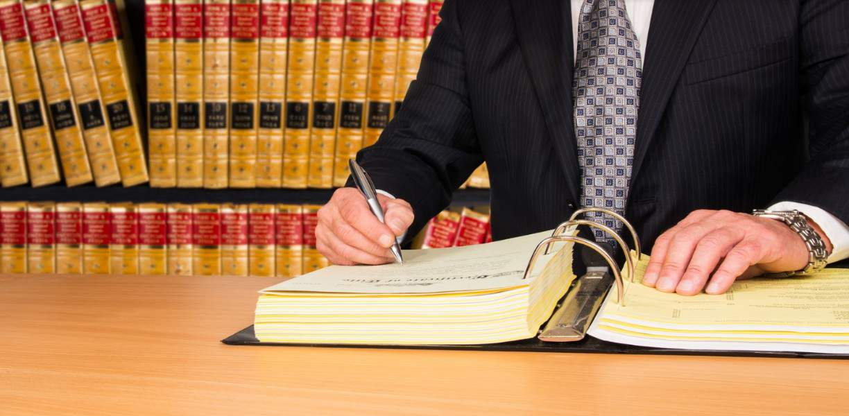lawyer writing on a book | Broomfield pedestrian accident attorneys