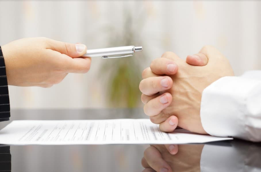 two people discussing over a piece of paper | Questions to Ask Your Personal Injury Attorney