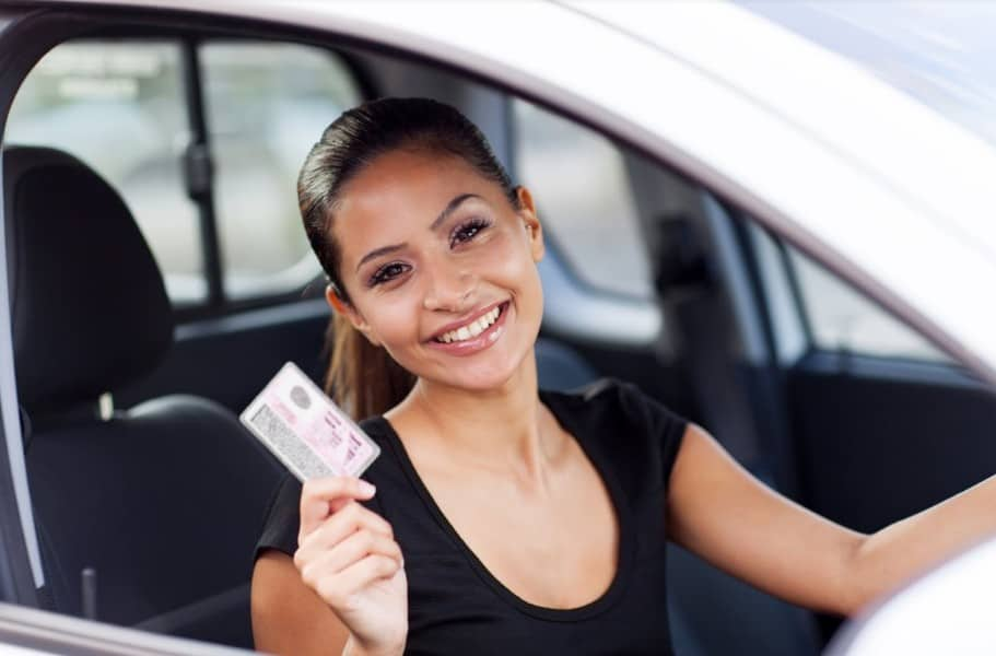 woman smiling while holder her driver license | safest cities in colorado