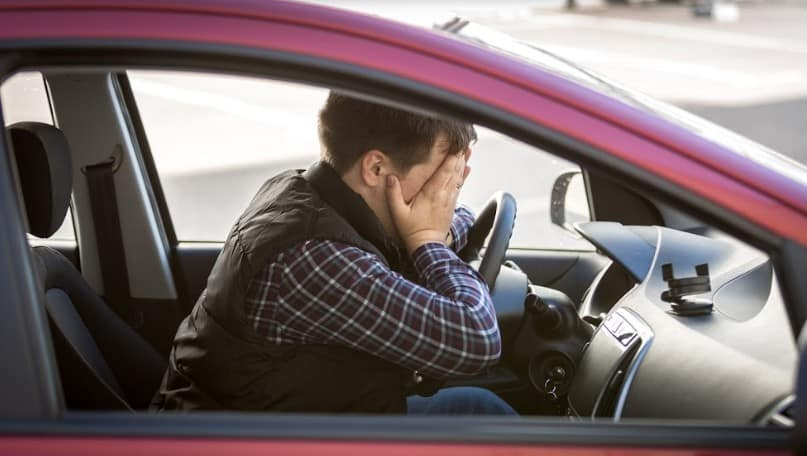 driver covering his face in frustration | driver liability for car accident